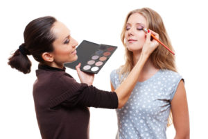 Make-up artist placing eye shadow on woman